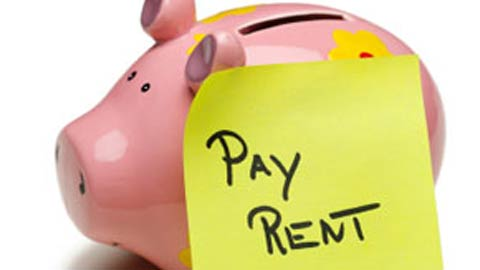 Piggy bank with a post-it note saying pay rent on it